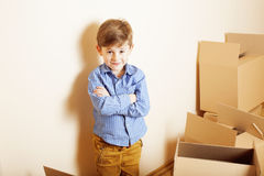 Little cute boy in empty room, remoove to new house. home alone emong boxes Royalty Free Stock Photography