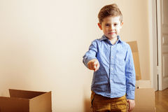 Little cute boy in empty room, remoove to new house. home alone emong boxes close up kid Royalty Free Stock Image