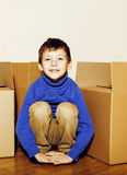 Little cute boy in empty room, remoove to new house. home alone emong boxes close up kid Stock Photos