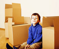 Little cute boy in empty room, remoove to new house. home alone emong boxes close up kid smiling. Close up royalty free stock images