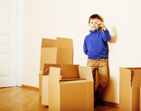 Little cute boy in empty room, remoove to new house. home alone emong boxes close up kid smiling. Close up royalty free stock image