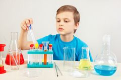 Little cute boy is engaged in chemical experiments in laboratory Stock Photos