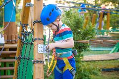 Little cute boy enjoying activity in a climbing adventure park on a summer sunny day. toddler climbing in a rope playground stock photos