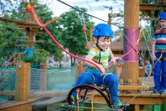 Little cute boy enjoying activity in a climbing adventure park on a summer sunny day. toddler climbing in a rope playground royalty free stock photo