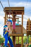 Little cute boy enjoying activity in a climbing adventure park on a summer sunny day. toddler climbing in a rope playground stock images