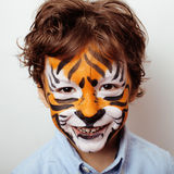 Little cute boy with faceart on birthday party close up, little cute tiger Royalty Free Stock Images
