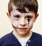 Little cute boy with facepaint like zombie apocalypse at hallowe. Little cute real boy with facepaint like zombie apocalypse at halloween party close up, treat Royalty Free Stock Photo