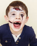Little cute boy with facepaint like zombie apocalypse at hallowe. Little cute real boy with facepaint like zombie apocalypse at halloween party close up, treat Stock Photo