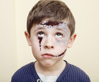Little cute boy with facepaint like zombie apocalypse at halloween party close up. On white background Royalty Free Stock Photography