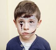 Little cute boy with facepaint like zombie apocalypse at halloween party close up. On white background Stock Photos