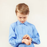 Little cute boy fastened the buttons on sleeve bright shirt Stock Photography