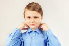 Little cute boy fastened collar of shirt. Little cute boy fastened collar of bright shirt stock photography