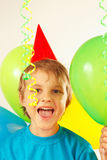 Little cute boy in festive hat with holiday balls and streamer Stock Images