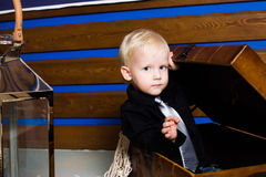 Little cute boy gets out of a pirate chest idea, childhood, bright, fun, kids, children Stock Image