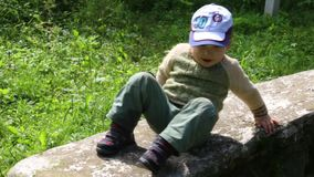 Little cute boy and girl slides down stone wall stock footage