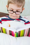 Little cute boy reading book in bed Royalty Free Stock Image