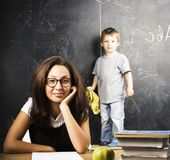 Little cute boy in glasses with young real teacher, classroom studying Stock Images