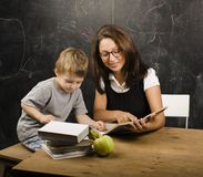 Little cute boy in glasses with young real teacher Stock Image