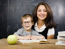 Little cute boy in glasses with young real teacher Stock Photography