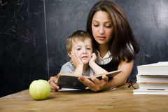 Little cute boy in glasses with young real teacher Stock Images