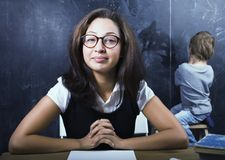 Little cute boy in glasses with young real teacher, classroom studying at blackboard school Stock Photography