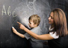Little cute boy in glasses with young real teacher Royalty Free Stock Photos