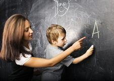 Little cute boy in glasses with young real teacher, classroom studying at blackboard school Royalty Free Stock Photo
