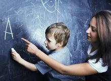 Little cute boy in glasses with young real teacher, classroom studying at blackboard school Stock Image