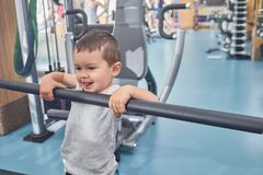 Little cute boy grimacing, holding on metallic crossbar in gym. Child laughing, smiling, looking cute, happy, satisfied. Heavy simulators standing behind royalty free stock photography
