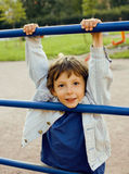 Little cute boy hanging on gymnastic ring. Close up Stock Photo