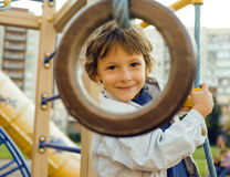 Little cute boy hanging on gymnastic ring Stock Images