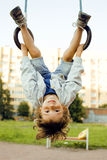 Little cute boy hanging on gymnastic ring Stock Photos