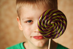 The little cute boy hides behind big sweet sugar. The little lovely boy hides behind big sweet sugar candy Stock Image