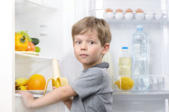 Little cute boy holding banana near open fridge Royalty Free Stock Photos