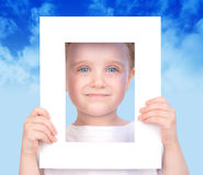 Little Cute Boy Holding Frame Picture. A little cut boy is holding a white frame and his face is looking through it. There are clouds in the background and he Royalty Free Stock Photos
