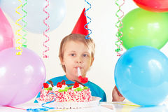 Little cute boy in holiday hat with birthday cake with whistle and festive balloons Royalty Free Stock Photography