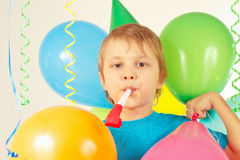 Little cute boy in holiday hat with whistle and festive balloons and streamer Stock Image