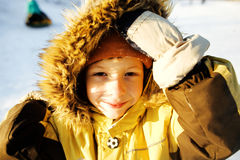 Little cute boy in hood with fur on snow outside Royalty Free Stock Photography