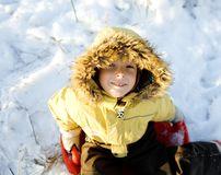 Little cute boy in hood with fur on snow outside Royalty Free Stock Image