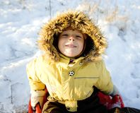 Little cute boy in hood with fur on snow outside Royalty Free Stock Photo
