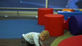 Little boy joyfully runs in the children's play area at the airport, slow motion. Little cute boy joyfully runs in the childre's play area among the big colorful stock footage