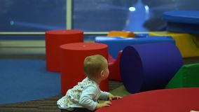 Cute boy joyfully runs in the children's play area at the airport in slow motion. Little cute boy joyfully runs in the children's play area among the big stock video footage