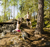 Little cute boy jumping with bungee in forest, training with dad, happy family on vacations in camp, father and son Stock Image