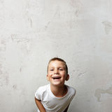 Little cute boy laughing at the camera. Cocrete Royalty Free Stock Photo