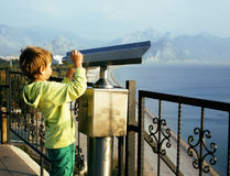 Little cute boy looking through telescope at sea viewpoint in Ataturk park Royalty Free Stock Photography