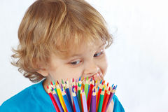 Little cute boy looks on color pencils Royalty Free Stock Photo