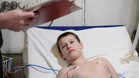 Little boy lying on hospital bed and smiling while listening to male doctor writing on clipboard stock video footage