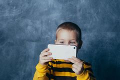 Little cute boy with a mobile phone takes a selfie and shows emotions royalty free stock photos