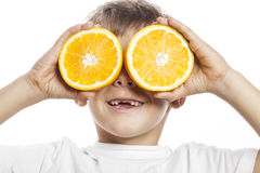 Little cute boy with orange fruit double isolated on white smiling without front teeth adorable kid cheerful Stock Image