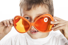Little cute boy in orange sunglasses pointing Royalty Free Stock Photography